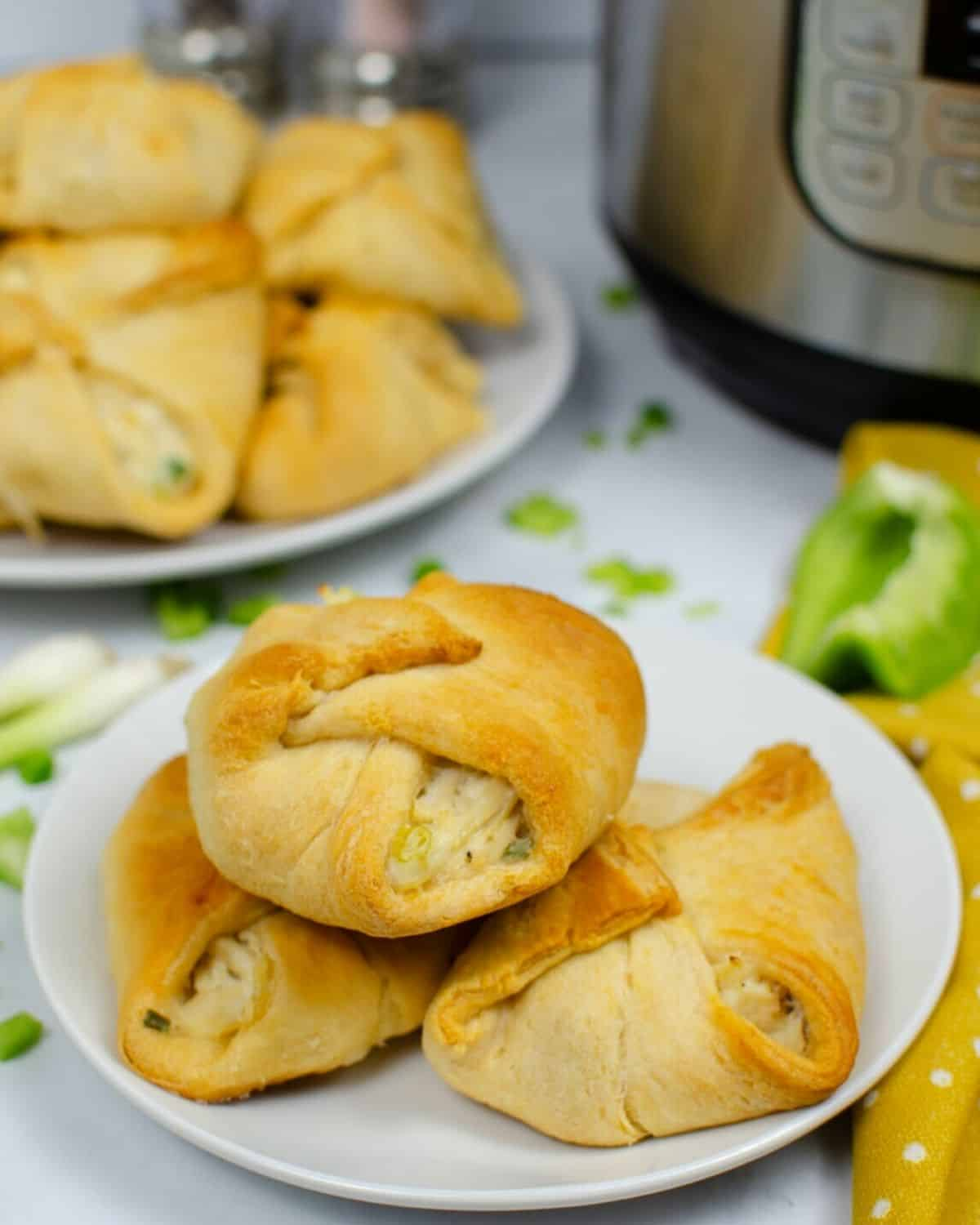 A large white plate with buttery crescent rolls stuffed with shredded chicken in a cream sauce.
