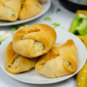 A trio of chicken stuffed crescent rolls on a plate with another plate behind it filled with chicken sandwiches.