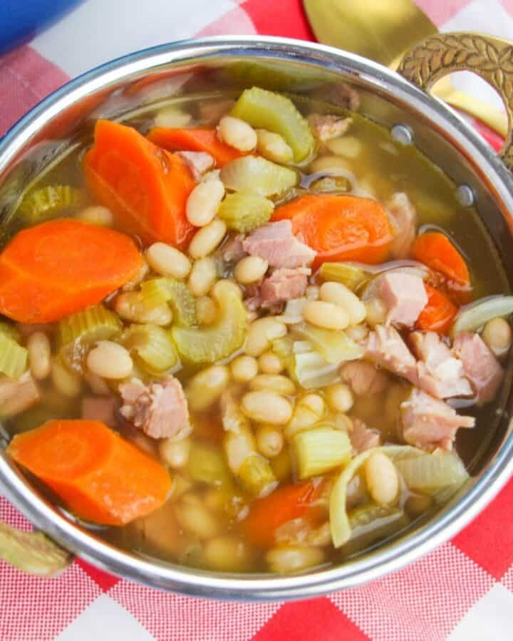 A silver bowl with gold handles filled with soup, carrots, celery, beans, and diced ham.
