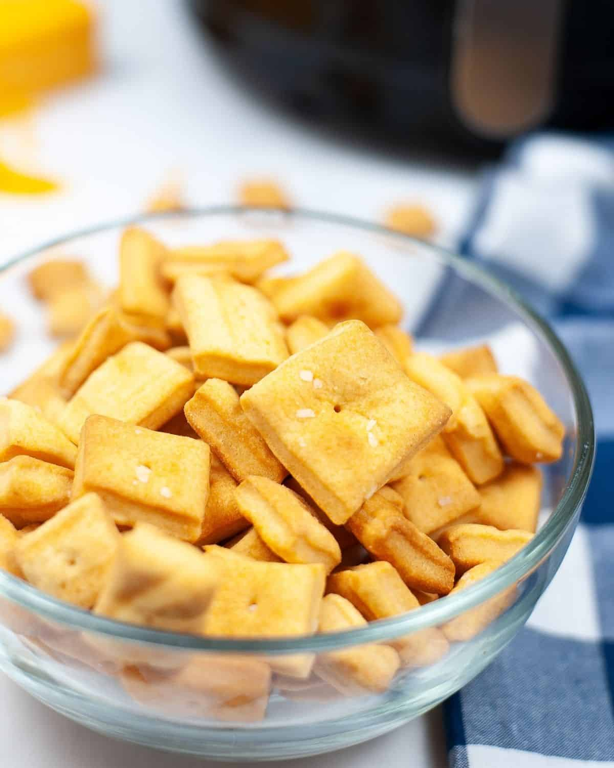 A side view of a glass bowl filled with homemade cheez-its.