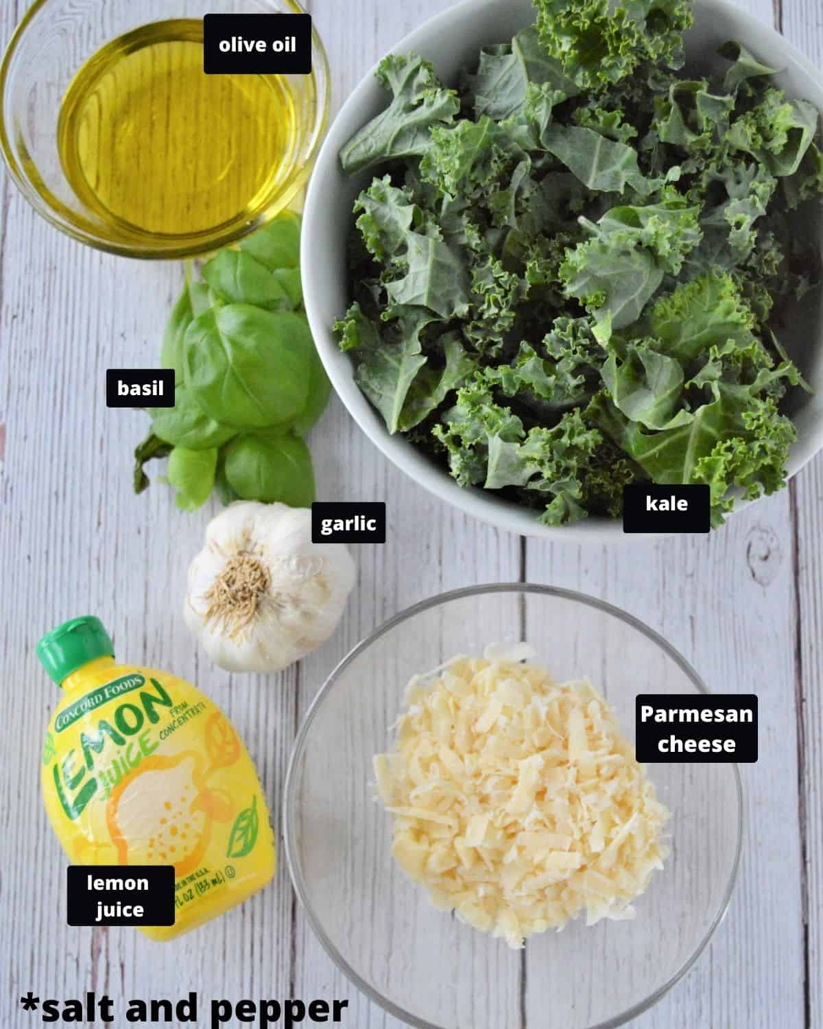 Ingredients on a white wooden table lemon juice, olive oil, Parmesan cheese, kale, basil, and garlic.