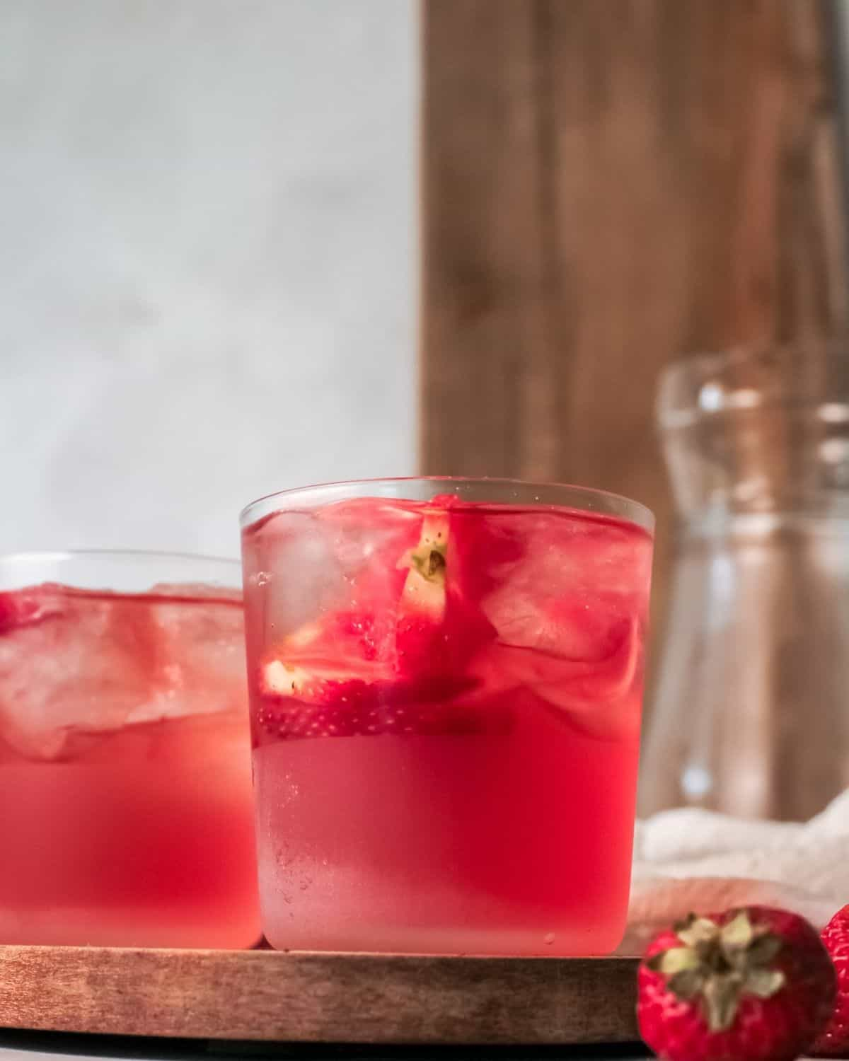 Two glasses filled with ice cubes, sliced strawberries, and strawberry sweet tea.
