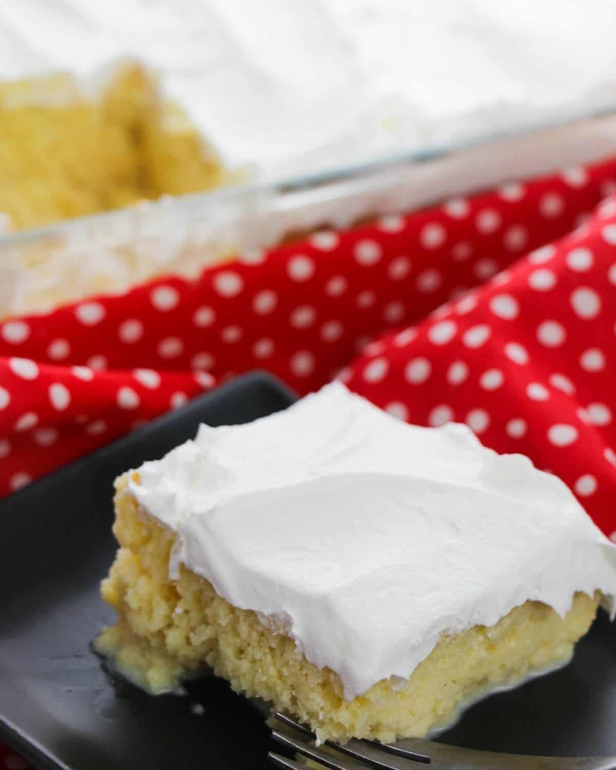 A slice of tres leches cake on a plate with a red polka dot napkin in the background.