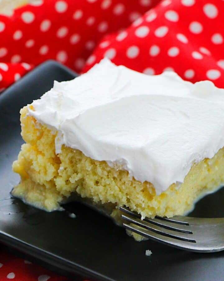 A slice of tres leche cake topped with whipped cream on a black plate.