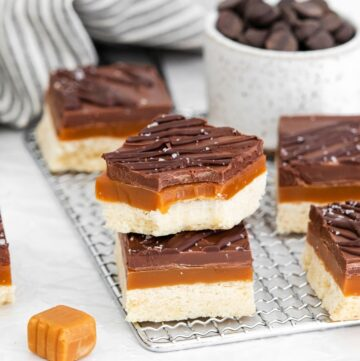 Layered homemade Caramel candy bars stacked on a wire rack.