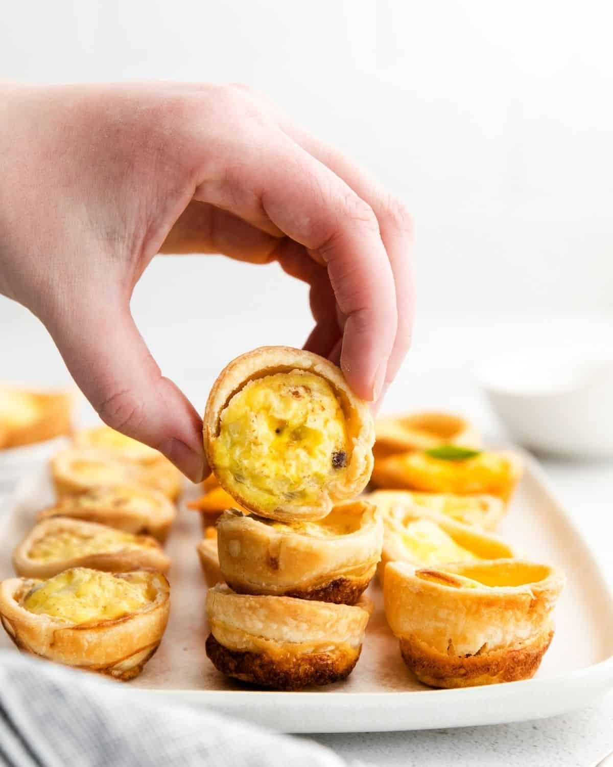 Mini quiche on a plate with one being held above the others.