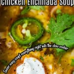 Enchilada soup in a white soup bowl topped with sour cream and sliced jalapeno.