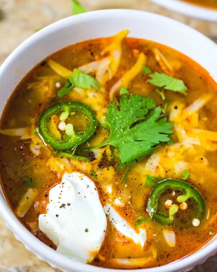 A white soup bowl fillled with enchilada soup topped with melted cheese and a dollop of sour cream.