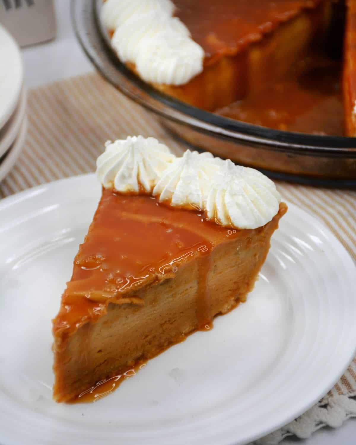 A slice of salted caramel pie topped with caramel and whipped cream.