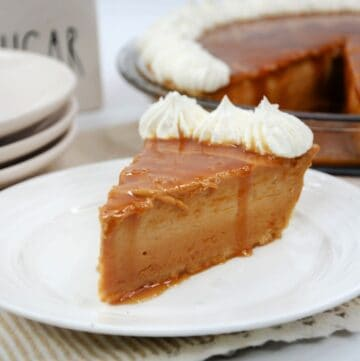 A slice of caramel pie with a whole caramel pie behind it.