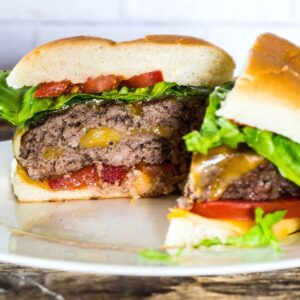 A cheese stuffed burger sliced in half topped with lettuce and tomatoes.