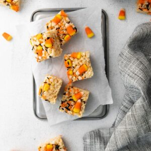 Festive cereal treats decorated for halloween with candy corn sprinkled around the rice treats.