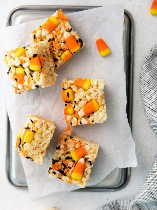 n overhead view of cut rice crispy treats decorated for Halloween on a piece of parchment paper.