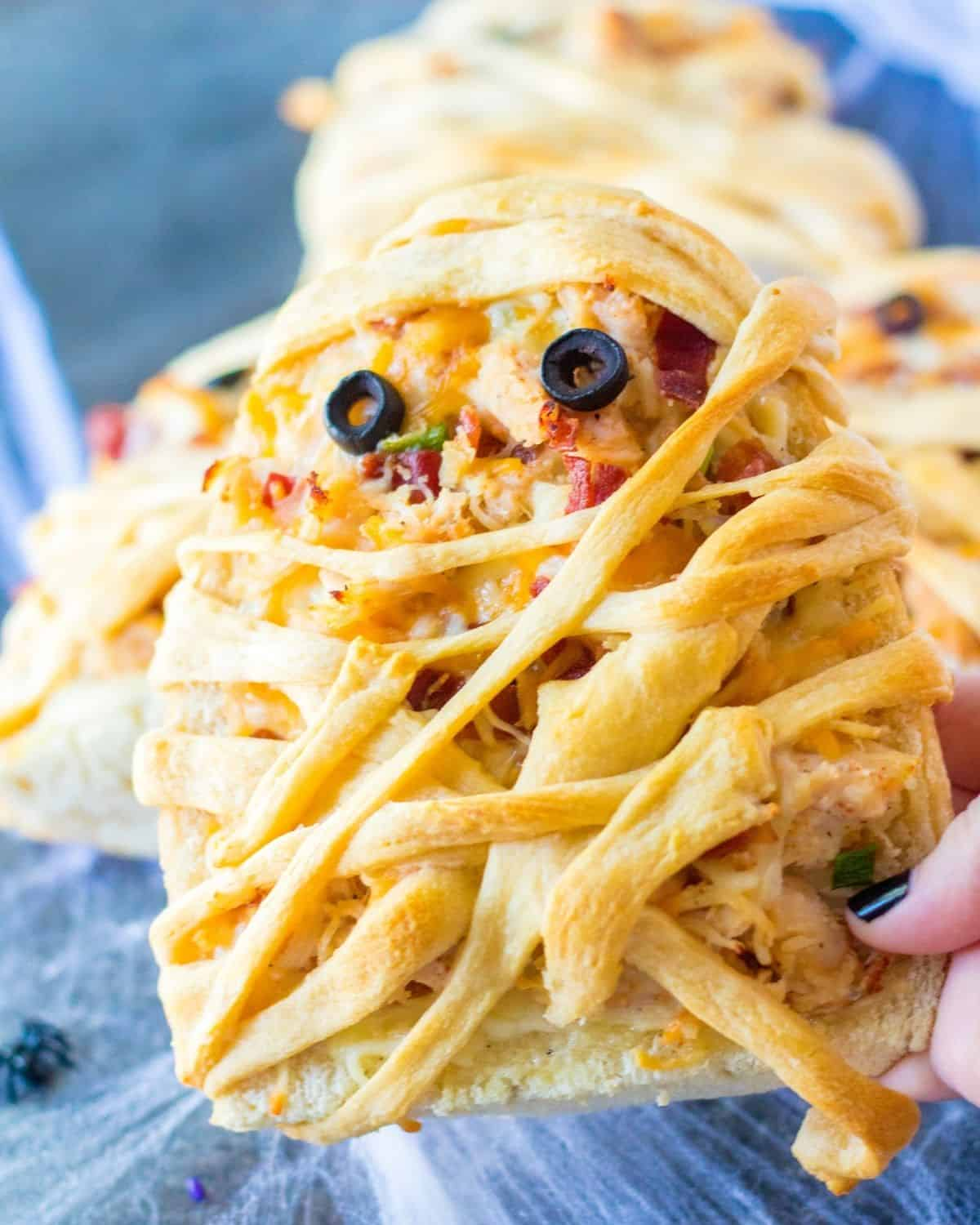 A hand holding up a french bread pizza with crescent roll strips wrapped around it to look like a mummy.