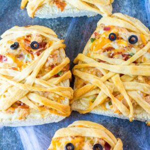 French bread pizza mummys on a blue linen napkin.
