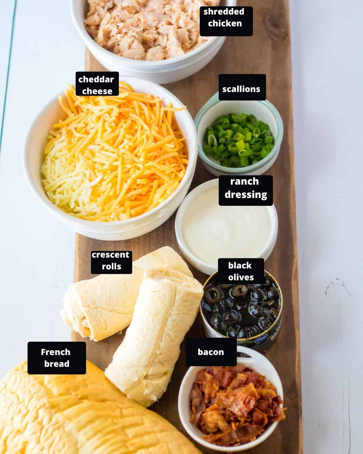 Ingredients to make mummy pizza on a wooden board, shredded chicken, cheddar cheese, black olives, scallions, crescent rolls, french bread, bacon, and ranch dressing.