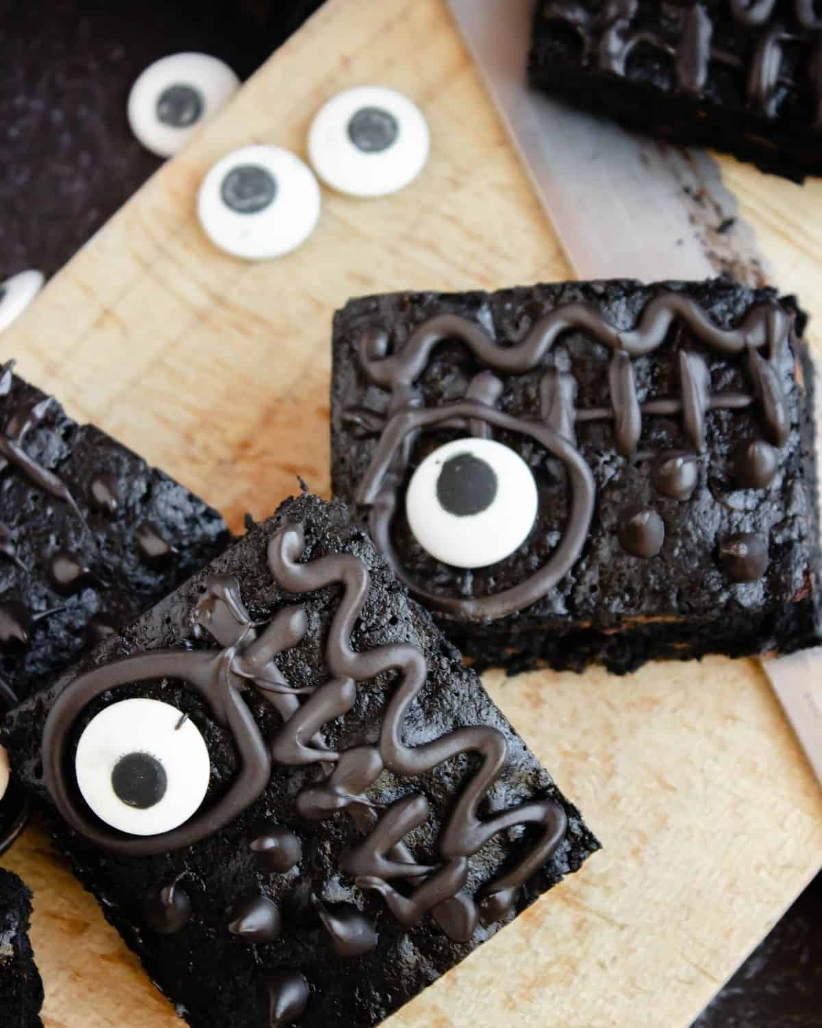 Brownie squares with candy eyes and chocolate designs on the brownie.