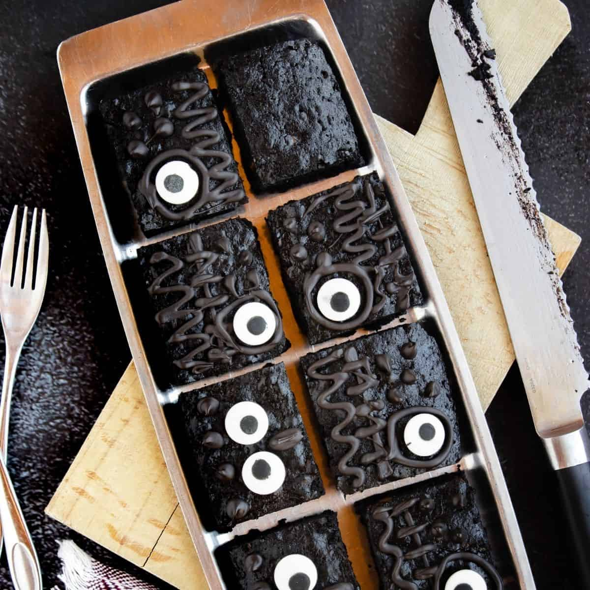 Hocus Pocus brownies cut into squares and being decorated with candy eyes and chocolate decorations.