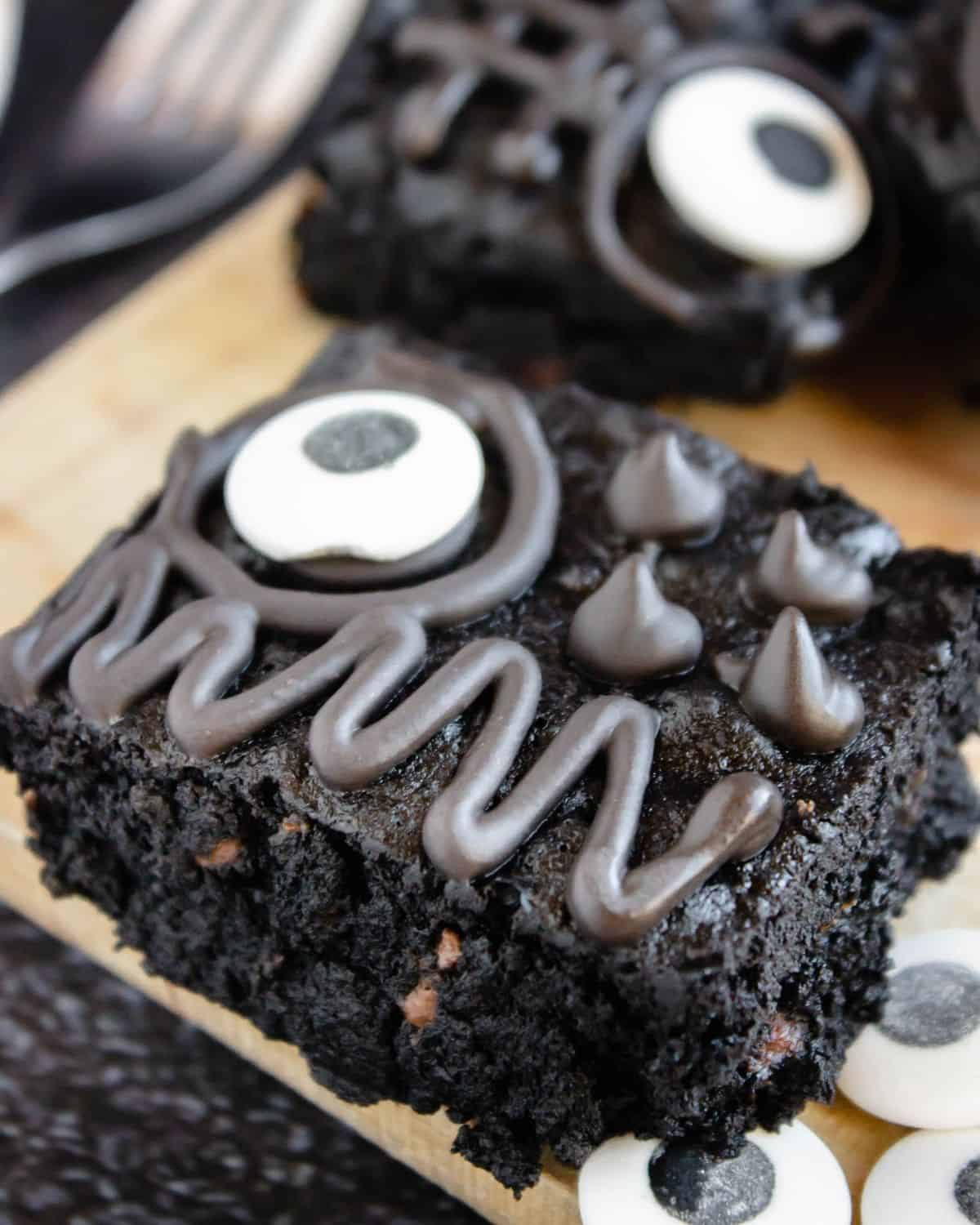 A brownie slice on a wooden board topped with a candy eye ball and chocolate icing design.