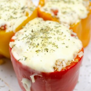 A side view of a red pepper stuffed with rice and topped with melted mozzarella.