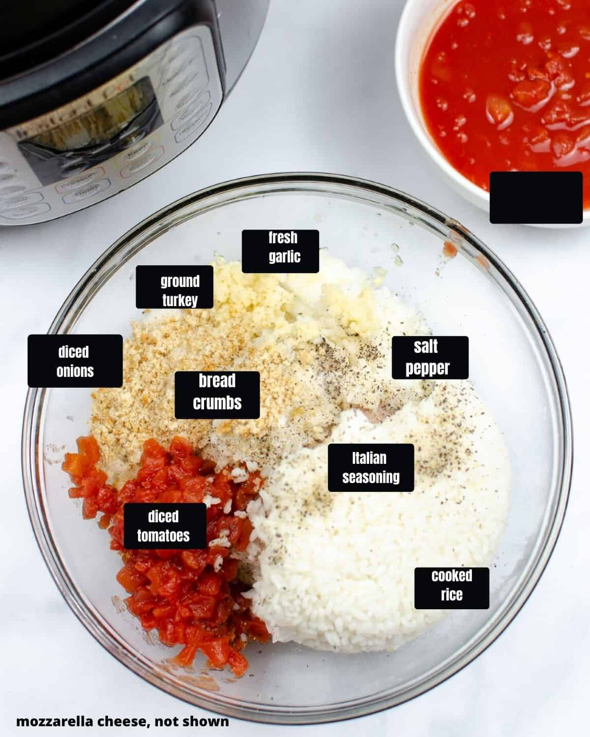 A glass mixing bowl with diced onions, bread crumbs, salt, pepper, Italian seasoning, Rice, garlic and ground turley.