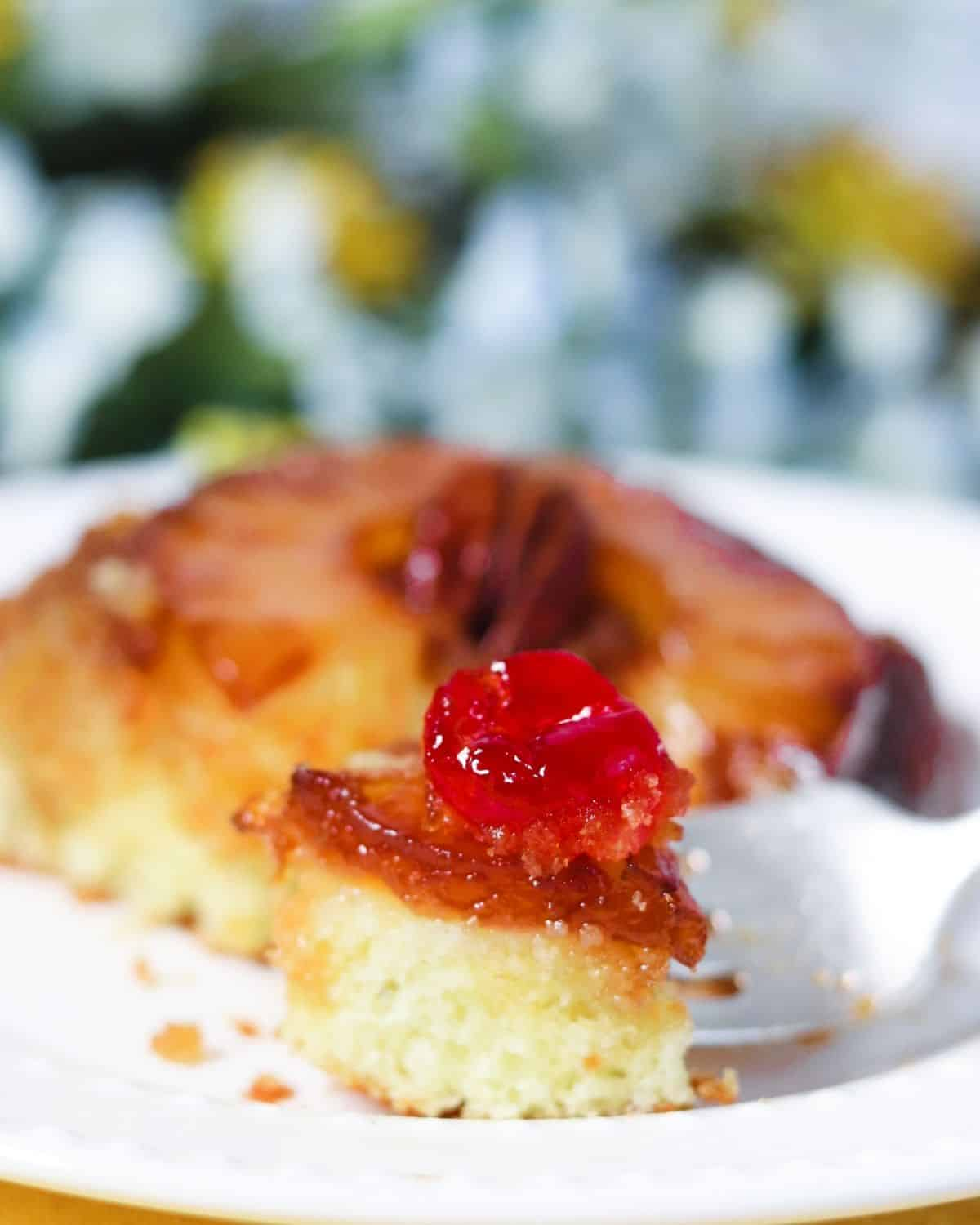 A silver fork with a piece of yellow cake topped with a maraschino cherry on the fork with the cake in the background.