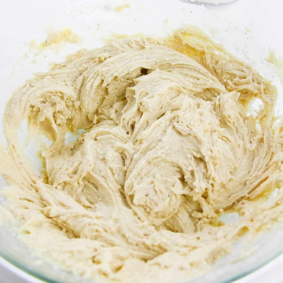 Vanilla cake mix that has been whipped in a glass bowl.